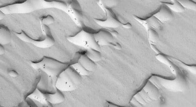 NASA's Mars Global Surveyor shows frost-covered sand dunes in Chasma Boreale in the early northern spring season on Mars. Dark spots, some of them with bright halos of re-precipitated frost, have formed as the dunes begin to defrost.