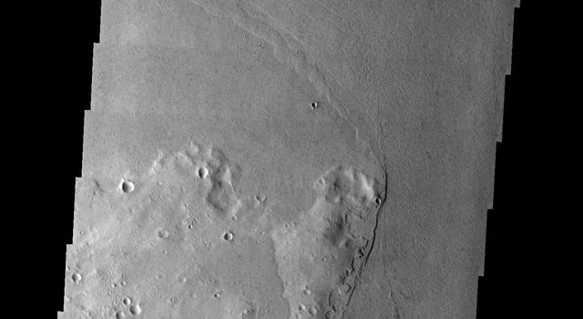 This image taken by NASA's 2001 Mars Odyssey shows craters and hills form high standing streamlined plateaus or islands in a channeled area on the martian landscape.