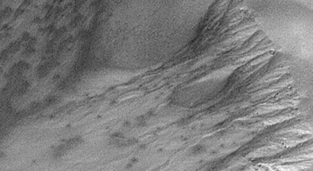NASA's Mars Global Surveyor shows frost-covered gullies in a crater in the martian southern hemisphere. The dark spots are areas where the frost has begun to change or sublime away.