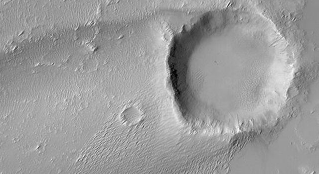 NASA's Mars Global Surveyor shows a streak formed by wind in the lee of a meteor impact crater on Mars.