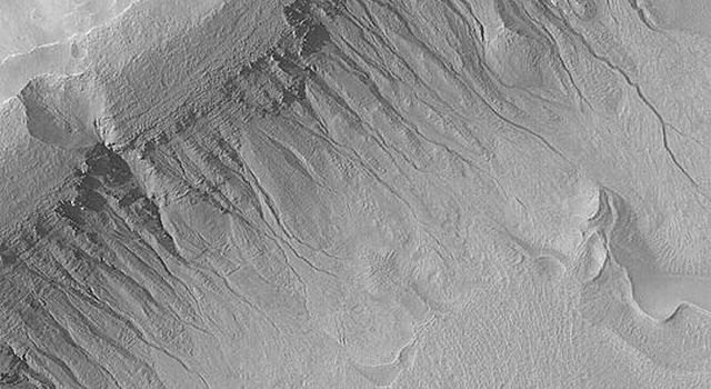 NASA's Mars Global Surveyor shows gullies in the wall of an impact crater in Terra Sirenum on Mars.
