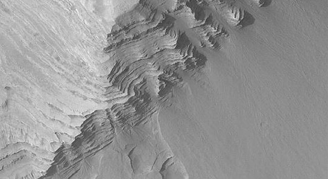 NASA's Mars Global Surveyor shows some of the layer outcrops in Terby Crater on Mars. Fans of debris have eroded from the steep, layered slopes in some places.