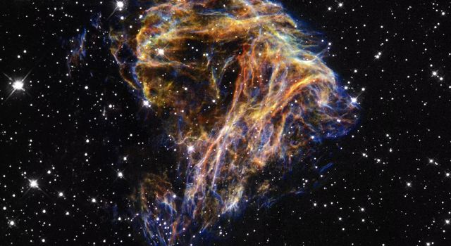 Resembling sparks from a fireworks display, this image taken by a JPL camera onboard NASA's Hubble Space Telescope shows delicate filaments that are sheets of debris from a stellar explosion in the nearby Large Magellanic Cloud galaxy.