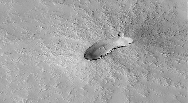NASA's Mars Global Surveyor shows a small, dust-covered volcano on the plains east of Pavonis Mons on Mars. The floor of the caldera (elliptical depression at the summit of the volcano) has a few windblown ripples on it.