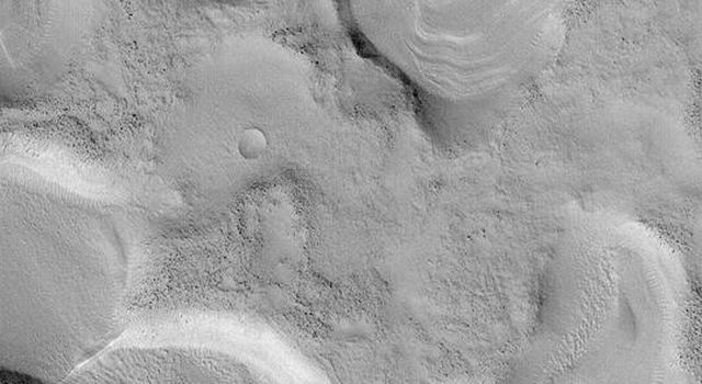 NASA's Mars Global Surveyor shows a cluster of old, small impact craters on Mars. The group of craters was probably formed by secondary impacts following a much larger impact that occurred some distance away.