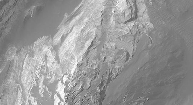 NASA's Mars Global Surveyor shows light-toned sedimentary rock outcrops on the floors of the chasms associated with the Valles Marineris system of Mars and neighboring outflow channels.