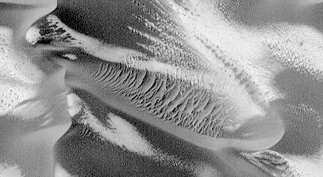 NASA's Mars Global Surveyor shows retreating patches of frost on a field of large, dark sand dunes in the Noachis region of Mars. Large, windblown ripples of coarse sediment are also seen on some of the dunes.