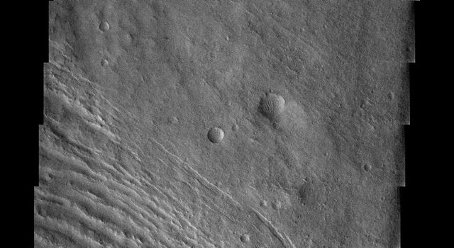 NASA's Mars Odyssey spacecraft captured this image in July 2003, showing the strange landscape of the eroding Medusa Fossae Formation. In the southern portion, small mounds of sedimentary material are all that remains of a once more continuous layer.