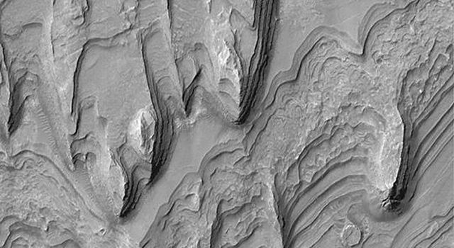NASA's Mars Global Surveyor shows a mound of layered sedimentary rock that stands higher than the rim of Gale crater on Mars.