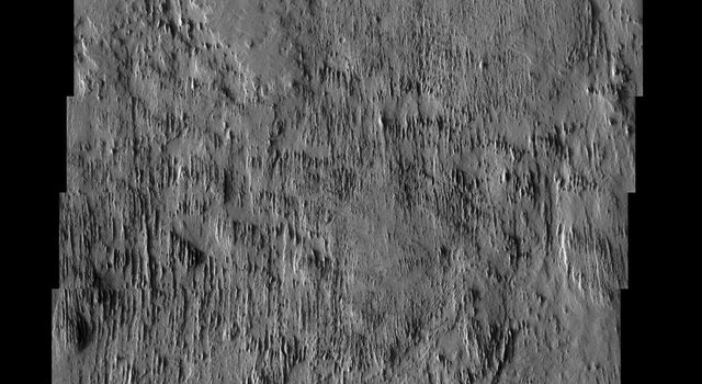 NASA's Mars Odyssey spacecraft captured this image in August 2003, showing parallel grooves oriented north to south, slowly eroded by winds of the same alignment. At bottom, a round mesa is most likely an inverted crater on Mars.
