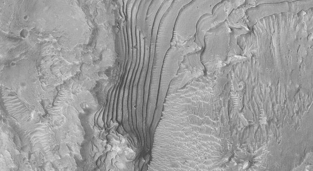NASA's Mars Global Surveyor shows an outcropping of ancient, sedimentary rock in a crater in western Arabia Terra on Mars.