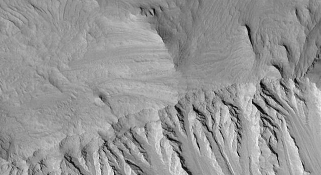 NASA's Mars Global Surveyor shows eroded, layered sedimentary rock exposures, common in the chasms of the Valles Marineris system on Mars.