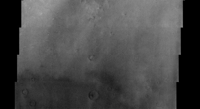 NASA's Mars Odyssey spacecraft captured this image in September 2003, showing bright wind streaks in the lee of craters and other obstacles in this image, located in Sinus Sabaeus, near the Martian equator.