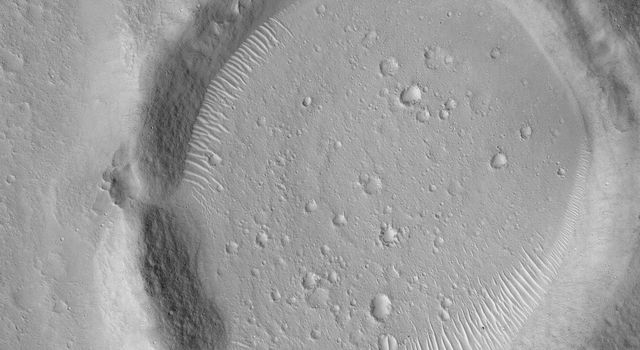 NASA's Mars Global Surveyor shows an old, eroded meteor impact crater in western Chryse Planitia on Mars.