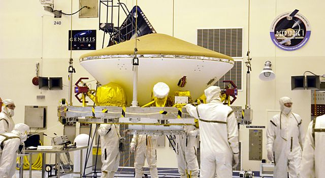 Suspended by an overhead crane in the Payload Hazardous Servicing Facility, the Mars Exploration Rover (MER) aeroshell is guided by workers as it moves to a rotation stand.