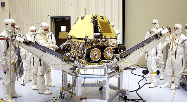 In the Payload Hazardous Servicing Facility, technicians reopen the lander petals of the Mars Exploration Rover 2 (MER-2) to allow access to one of the spacecraft's circuit boards.