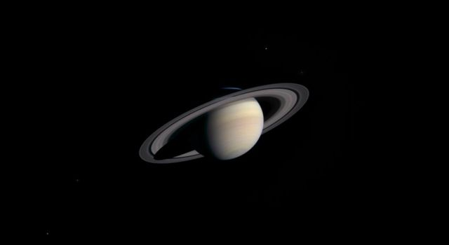 A cold, dusky Saturn looms in the distance in this striking, natural color view of the ringed planet and five of its icy satellites. This image was taken by NASA's Cassini's narrow angle camera on Nov. 9, 2003, from a distance of 111.4 million kilometers.