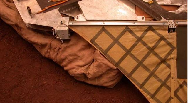 This image shows the deflated airbags retracted underneath the lander petal at the JPL In-Situ Instrument Laboratory.