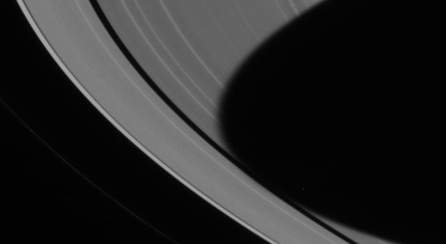 The dark shadow of Saturn's southern hemisphere spreads across the planet's rings all the way to the Encke gap. This image was captured by NASA's Cassini spacecraft narrow angle camera on June 21, 2004.