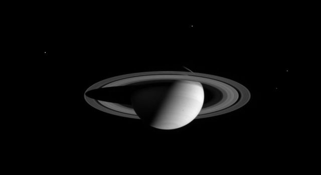 Saturn wears a halo of four moons in this wide angle camera image taken by NASA's Cassini spacecraft on August 18, 2004.