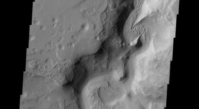 This image, part of an images as art series from NASA's 2001 Mars Odyssey released on March 25, 2004 shows part of the Auqakuh Vallis region on Mars. The image shows the presence of liquid or ice carved channels and some dunes.