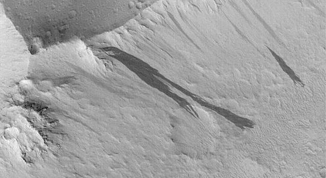 NASA's Mars Global Surveyor shows dark slope streaks on ridges in the Lycus Sulci region, north of the Olympus Mons volcano. Slope streaks form in the dry, dust-mantled regions of Mars.