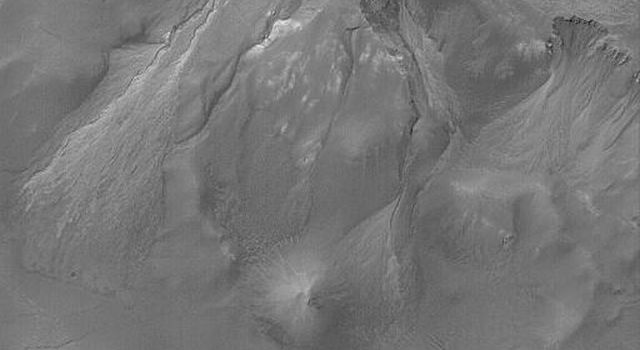 NASA's Mars Global Surveyor shows a set of south middle-latitude gullies in a crater wall on Mars. Some of the gullies and the erosional alcoves that formed above them have cut and exposed a light-toned material.