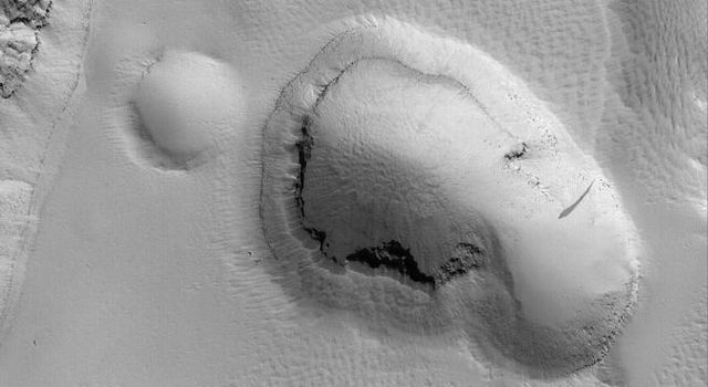 NASA's Mars Global Surveyor shows a pit formed by collapse on the lower southeast flank of Olympus Mons on Mars. The terrain surrounding the pit, and the pit walls and floor, appear to be mantled by fine dust.