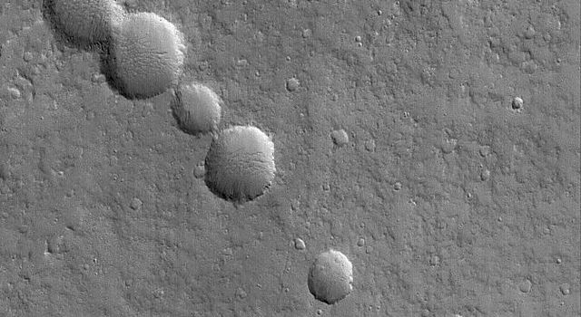 NASA's Mars Global Surveyor shows a chain of collapse pits on the lower northeast flank of the large martian volcano, Olympus Mons.
