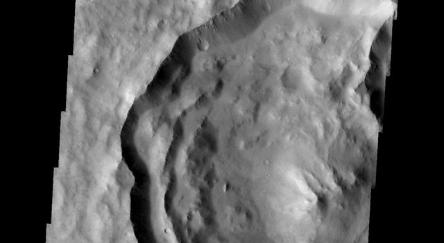 This image from NASA's 2001 Mars Odyssey released on April 21, 2004 shows a large crater on Mars in Memnonia Fossae that contains lobates situated on the mid-left hand side of the image.