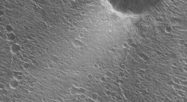 NASA's Mars Global Surveyor shows thin deposits of bright dust forming tails in the lee of craters in Acidalia Planitia on Mars.