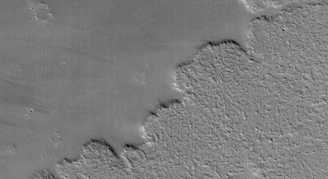 NASA's Mars Global Surveyor shows details on large lava flows in the Tharsis volcanic region of Mars.