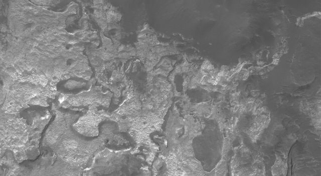NASA's Mars Global Surveyor shows light-toned, somewhat layered rock outcrops on the north wall of Columbus Crater on Mars. Remnants are found all around the walls of the crater, and at least one small remnant has been spotted on the crater floor.