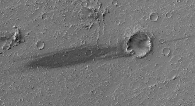 NASA's Mars Global Surveyor shows a dark wind streak on the lee (downwind) side of a small meteor impact crater in western Daedalia Planum on Mars. The substrate in this region consists of large lava flows.