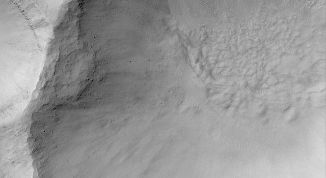 NASA's Mars Global Surveyor shows a martian gullied crater wall at southern mid-latitude. Formation of such gullies might have involved flowing liquid water.