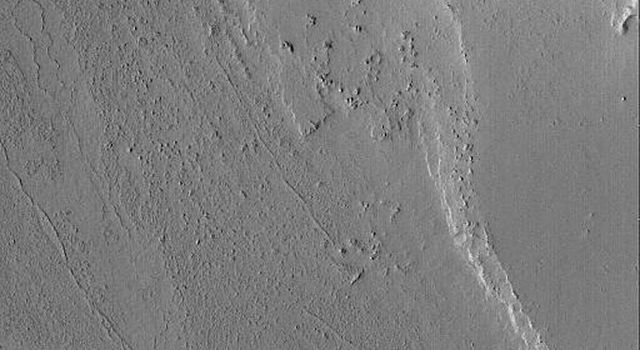 NASA's Mars Global Surveyor shows a portion of a channel in the Marte Valles outflow system on Mars. An old meteor impact crater blocked the erosive fluids that poured through Marte Vallis, creating a streamlined tail in its lee.
