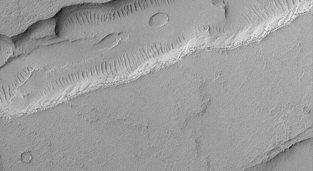 NASA's Mars Global Surveyor shows troughs and a pit chain (on the floor of the deeper trough) located immediately northeast of the giant Tharsis volcano, Arsia Mons on Mars.