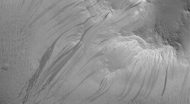 NASA's Mars Global Surveyor shows dark slope streaks coming off of rugged hills in the Lycus Sulci region, north of the Olympus Mons volcano on Mars.