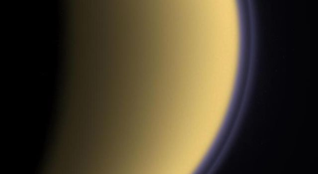 Encircled in purple stratospheric haze, Titan appears as a softly glowing sphere in this colorized image taken one day after NASA's Cassini spacecraft first flyby of the moon on July 2, 2004.