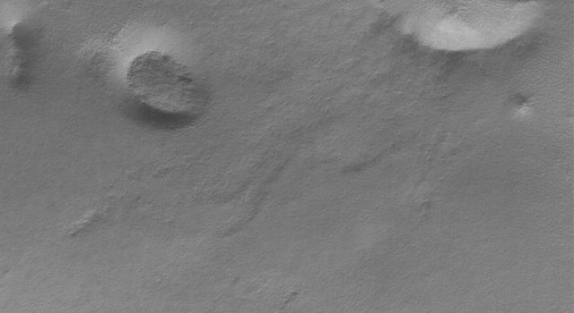 NASA's Mars Global Surveyor shows a summer scene from the south polar region of Mars. The circular feature in the northeast (upper right) corner of the image is an old meteor impact crater that has been partially filled and buried.