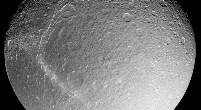 As it zoomed in on Saturn's moon Dione for a close flyby, NASA's Cassini spacecraft captured a set of images of the icy moon which have been combined into a mosaic here to provide a stunningly detailed global view.