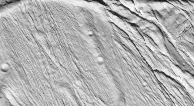 NASA's Cassini spacecraft took this image of the ropy, taffy-like topography on Saturn's moon Enceladus as it soared above the icy moon on Feb. 17, 2005.