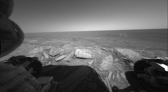 NASA's Mars Exploration Rover Opportunity looks back out at the plains of Meridiani Planum from the rover's first dip inside the rim of 'Endurance Crater.' Opportunity's rear hazard-avoidance camera took this picture on June 8, 2004.