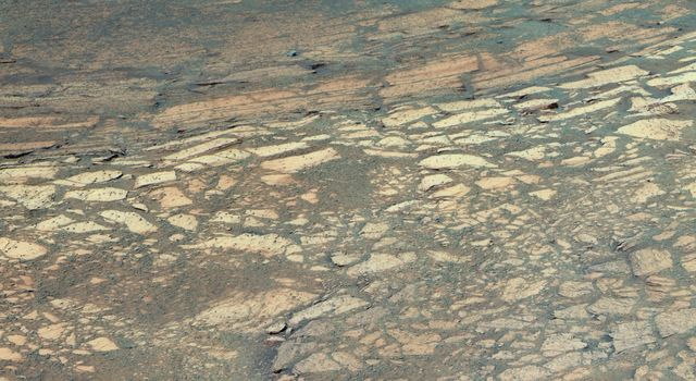 This image from NASA's Mars Exploration Rover Opportunity shows a hole it drilled into a flat rock dubbed 'Tennessee' on Mars. At least three distinct bands of rock visible in front of the rover.