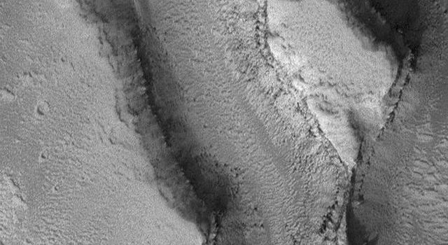 NASA's Mars Global Surveyor shows landforms in the Granicus Valles region, west of the Elysium volcanoes on Mars. Layered rock and some large, dark boulders are among the features observed.