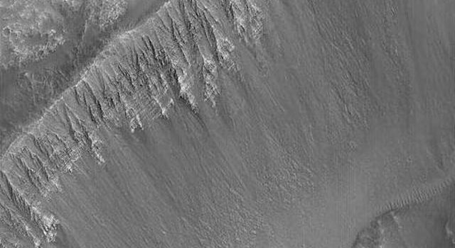 NASA's Mars Global Surveyor shows a fantastic outcrop of alternating light and dark layers in the wall of a crater that impacted into the floor of one of the eastern Kasei Valles flood channels on Mars.