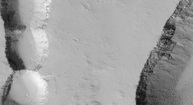 NASA's Mars Global Surveyor shows collapse pits and troughs on the lower northeast flank of the giant martian volcano, Ascraeus Mons on Mars.