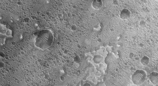 NASA's Mars Global Surveyor shows small buttes and irregular mesas on the floor of a crater in the Nili Fossae region of Mars.