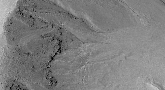 NASA's Mars Global Surveyor shows gullies with banked and somewhat sinuous channels and inner channels cut into the wall of a south middle-latitude crater on Mars.
