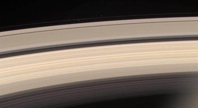 Saturn and its rings are prominently shown in this color image, along with three of Saturn's smaller moons. This image was taken on June 18, 2004, with NASA's Cassini spacecraft's narrow angle camera, 8.2 million kilometers from Saturn.